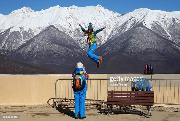 A volunteer jumps in the air as she poses for her friend at Gorky Gorod 960 prior to the Sochi 2014 Winter Olympics at the Mountain Cluster on...