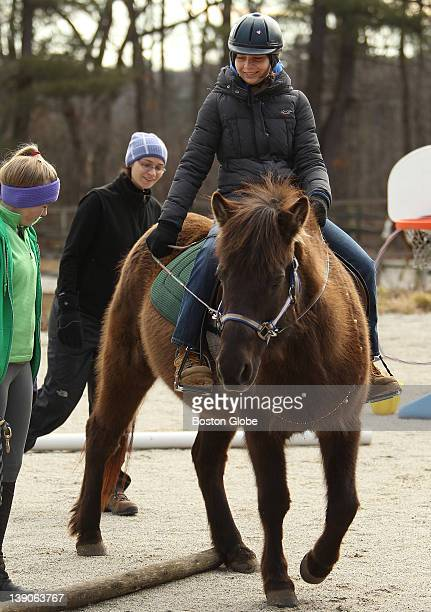 Volunteer Kailyn Stephens of Mendon and instructor Nicole Majkut right walk alongside Jona Ghelli of Holliston at Equine Partners a therapeutic...