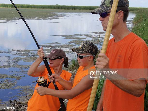 Volunteer Karen Fischer assists Tyler McCurdy of Loxahatchee Florida reel in a big alligator in southwestern Palm Beach County Florida as Tyler's dad...