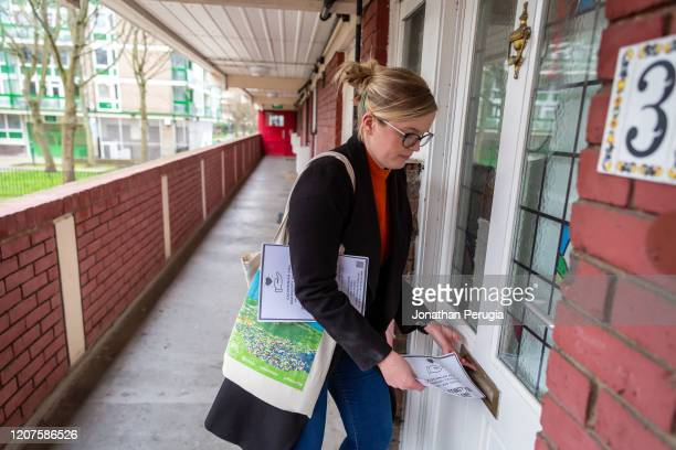 Volunteer Katherine Gilroy posts leaflets for a local community support group called Mutual Aid through letter boxes on a housing estate near the...