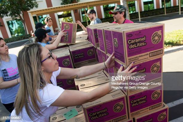 Volunteer Katie O'Neill of Orange, and several of her First American Title co-workers stack Caramel deLites as they load up vehicles during the Girl...