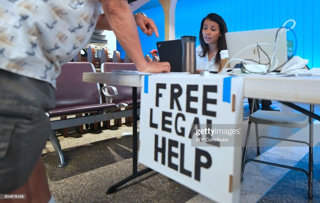 Volunteer lawyer Marwa Rifahie, a Civil Rights Attorney with the Council on American-Islamic Relations, responds to questions unrelated to the travel ban issue from behind a at a table set up at the International Arrivals section at Los Angeles International Airport in Los Angeles, California on June 30, 2017, offering free legal advice. Lawyers and rights activists took up positions at major US airports as a weakened version of President Donald Trump's travel ban took effect late Thursday. Attorneys working pro-bono set up makeshift, just-in-case legal aid stations -- some with signs in Arabic -- at airports serving New York, Los Angeles, San Francisco, Chicago, Washington and other cities, news reports said. /