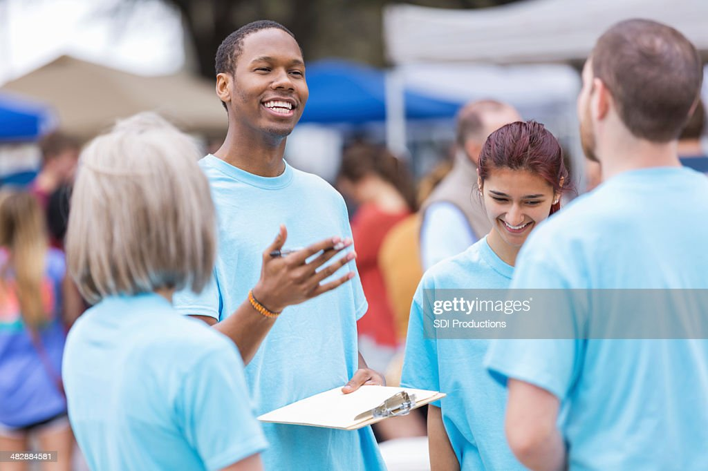 Volunteer leader giving instructions at outdoor festival or market : Stock Photo