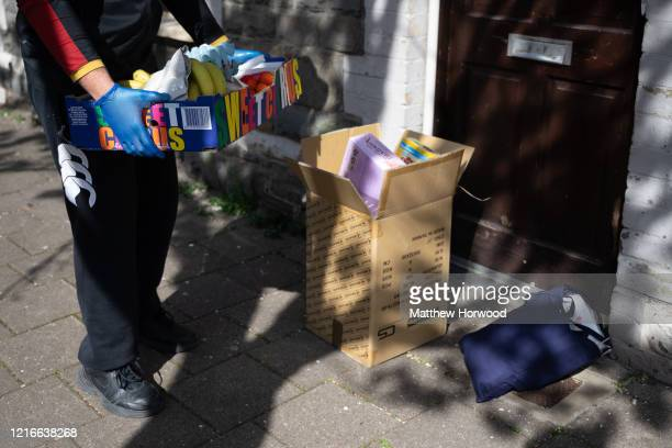A volunteer leaves a food delivery at the door of a family who are selfisolating on April 3 2020 in Cardiff Wales Staff and volunteers at Cardiff...