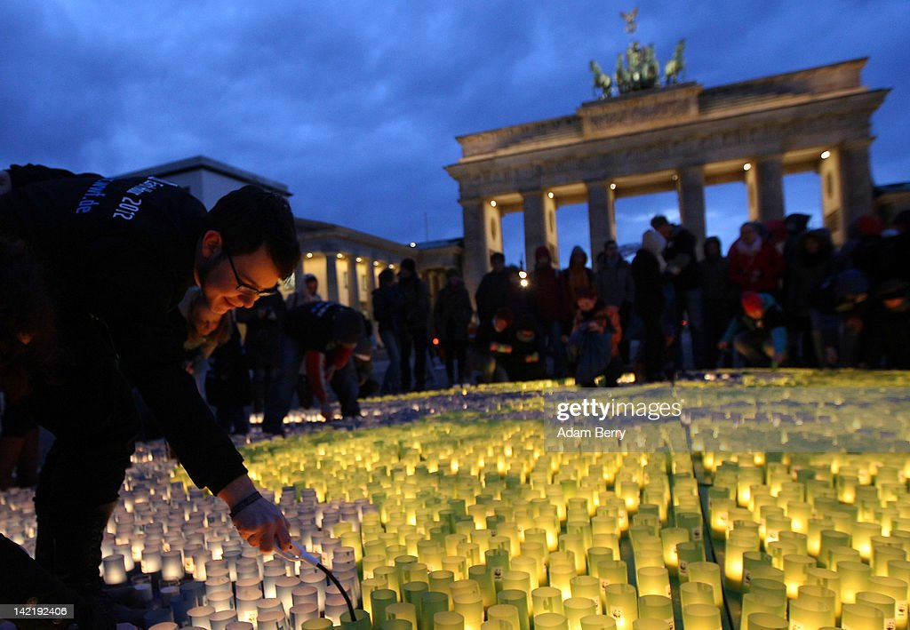 A volunteer lights one of 5000 blue and green candles in an eight-meter shape of Planet Earth in front of the Brandenburg Gate during Earth Hour 2012 on March 31, 2012 in Berlin, Germany. According to organizers, Earth Hour 2012 has participants including individuals, companies and landmarks in 147 countries and territories and over 5,000 cities agreeing to switch off their lights for one hour. The Brandenburg Gate, the Eiffel Tower in Paris, Big Ben Clock Tower in London, the Christ the Redeemer statue in Rio de Janeiro and the Empire State Building in New York are among the monuments whose operators have agreed to participate in the demonstration.