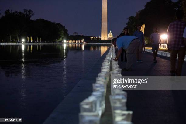 A volunteer lights up candles for the Lights of HOPE ceremony along the reflective pool beside the steps of the Lincoln Memorial on September 10 2019...