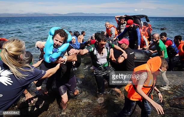 Volunteer Linda Blaack of Holland receives a child as Syrian migrants many of them refugees land after crossing the Mediterranean Sea arrive on the...