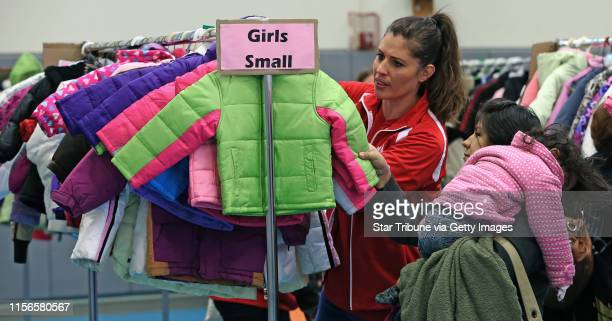 Volunteer Lisa Drevlow helped Valentina Zaragoza pick out a winter coat for her daughter Liliana age 2 who slept through the event during the annual...
