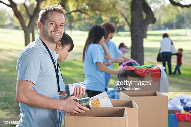 volunteer looking back while sorting through donations - meals on wheels stock pictures, royalty-free photos & images