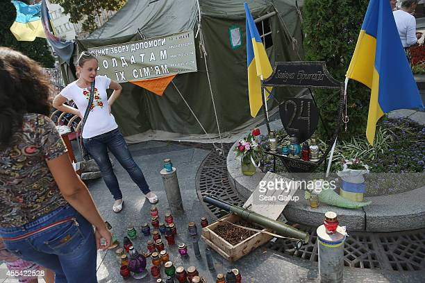 A volunteer looks at a memorial to the Ukrainian Army 24th Iron Brigade whose members are among units fighting in eastern Ukraine at a collection...
