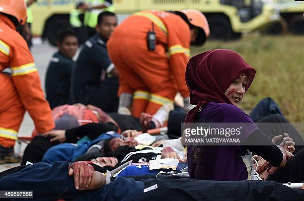 A volunteer looks on at a mock scene of an airplane crashsite during an emergency drill at the Kuala Lumpur International Airport in Sepang on...