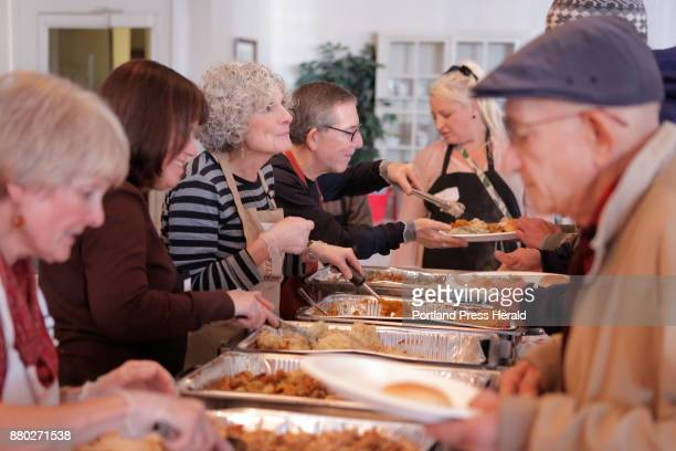 Volunteer Lynne Gammon, third from left, listens to an attendee while her husband Rick Gammon serves turkey to another attendee at a free...