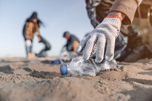 Volunteer man collecting trash on the beach. Ecology concept 1179252601