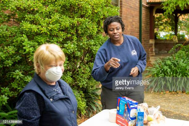 Volunteer Margaret Baseley helps a woman with her food order at St Paul's Anglican Church in Burwood on March 24 2020 in Sydney Australia The Parish...