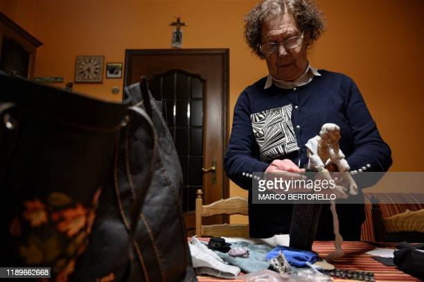 Volunteer Maria Franca Testa sews clothes on a nativity figure for the 43rd edition of the Presepio of Cavallermaggiore a 300sqm Christmas Nativity...