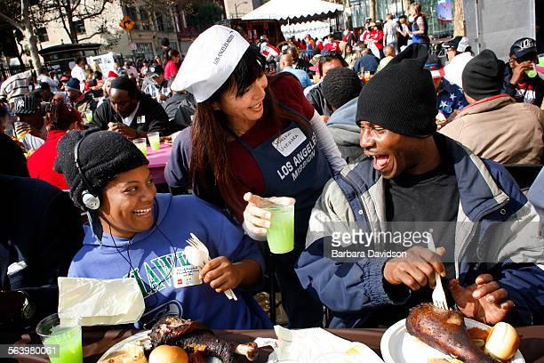 Volunteer Mariko Uyehara enjoys a fun conversation with Yasmine Villalovos and Edward Perry at the Los Angeles Mission annual Thanksgiving for the...