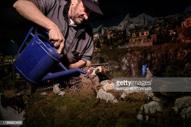 TOPSHOT Volunteer Mario Curcetti uses a watering can to set a small river at the 43rd edition of the Presepio of Cavallermaggiore a 300sqm Christmas...
