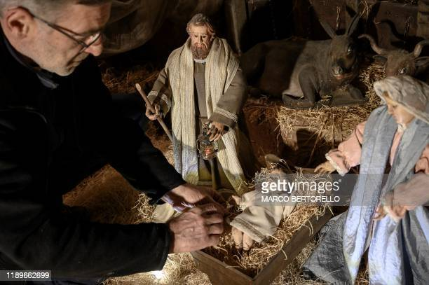 Volunteer Massimo Olocco sets a nativity figure for the 43rd edition of the Presepio of Cavallermaggiore a 300sqm Christmas Nativity crib in the...