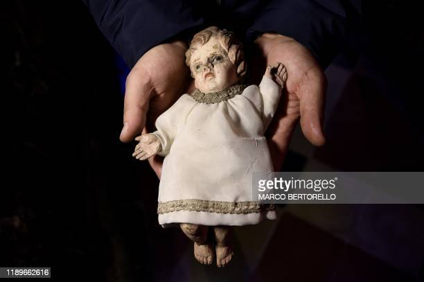TOPSHOT Volunteer Matteo Seia holds a nativity figure of Jesus one of the most ancient figures of the 43rd edition of the Presepio of...