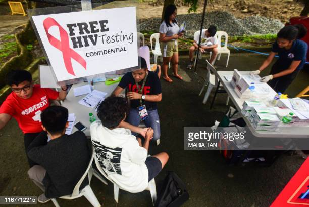 Volunteer medical technologists speak to students about a free HIV testing program at the State University in Manila on September 13 2019