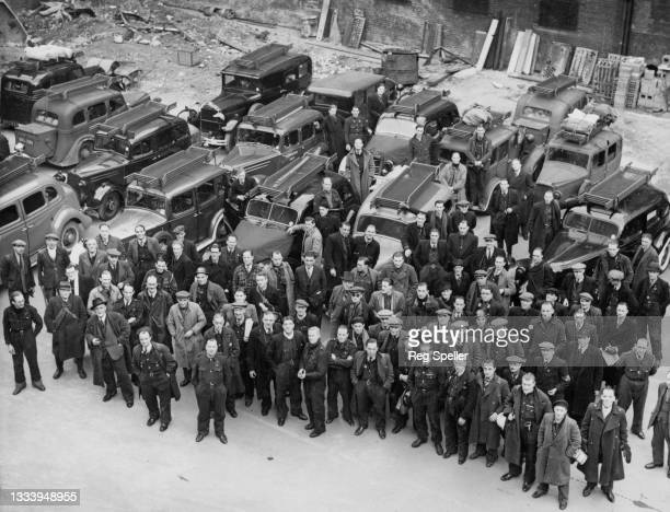 Volunteer members of the Auxiliary Fire Service of the London Fire Brigade pose for a photograph with their converted to fire engine motor vehicles...