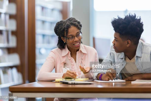 volunteer mentors teen boy in school library - role model stock pictures, royalty-free photos & images