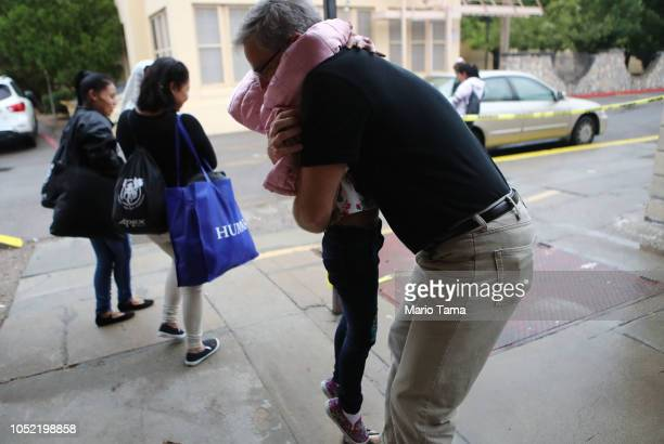 Volunteer Michael Brennan hugs a migrant child as she departs an Annunciation House shelter for migrants on October 12 2018 in El Paso Texas...