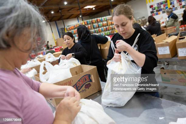 Volunteer Molly Matles packs food bags at the Alameda County Community Food Bank on Thursday, Jan. 17 in Oakland, Calif. The food bank is delivering...