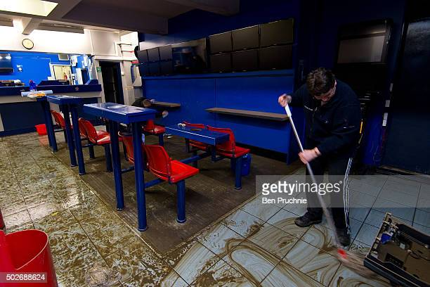A volunteer mops the floor of William Hill bookmakers on Tadcaster High Street on December 28 2015 in Tadcaster England Heavy rain over the Christmas...