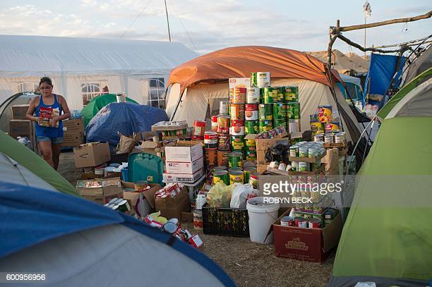 A volunteer moves food supplies in the main kitchen area of the Standing Rock Sioux protest encampment near Cannon Ball North Dakota where members of...