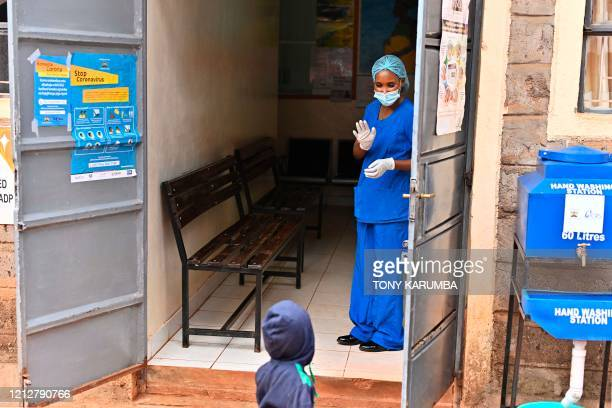 Volunteer nurse Anita Thumbi who is also an elected Member of County Assembly in the Nairobi County Government waves to a child while she waits for...