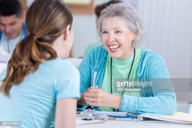 Volunteer nurse talks with patient during health fair