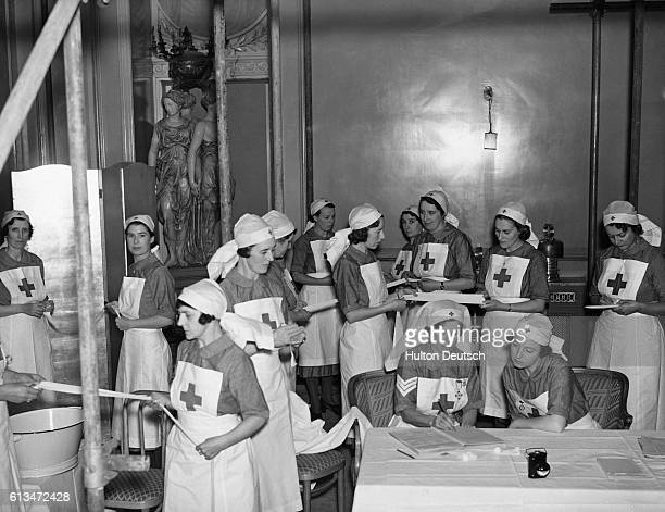 Volunteer nurses train in first aid procedures at a wartime aid station in the Pink Room of London's Savoy Hotel Most of the nurses come from the...