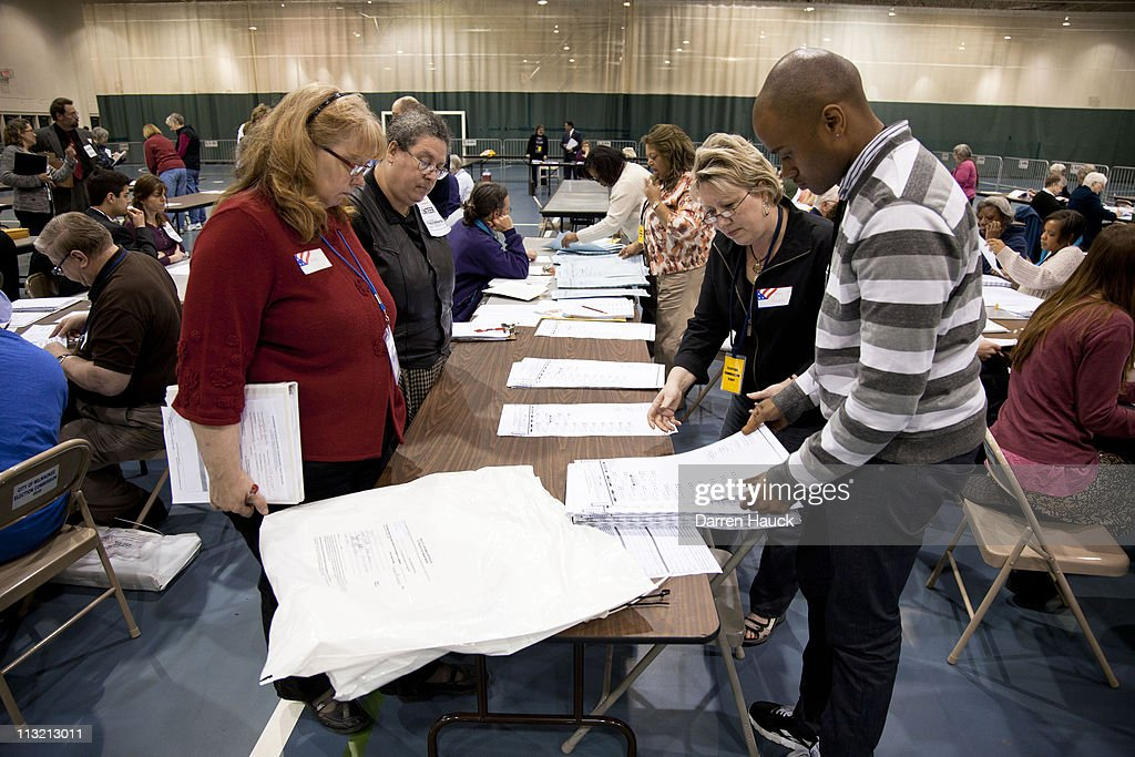 Volunteer observers (L) look on as members of the Milwaukee County Election Commission recount the ballots for the Wisconsin Supreme Court race between incumbent Justice David Prosser and Assistant Attorney General JoAnne Kloppenburg at the Milwaukee County Sports Complex April 27, 2011 Milwaukee. Observers from the Prosser and Kloppenburg campaign were overseeing the process to validate the recount.