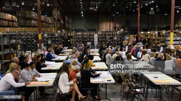 Volunteer observers view the process as election workers at tables examine ballots during a hand recount of votes cast in the US Senate race in Palm...