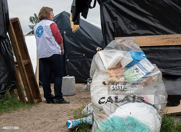 A volunteer of humanitarian NGO Medecins du Monde stands near a bin bag reading City of Calais on July 7 in the site dubbed new jungle where migrants...