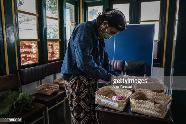 Volunteer of Kraton Palace of Yogyakarta, known as 'Abdi Dalem' prepares meat into bamboo baskets to distribute during celebrations for Eid al-Adha...