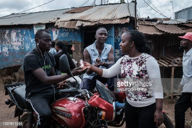 Volunteer of local NGO Shining Hope for Communities provide hand disinfectant to a man on a motorcycle as a preventive measure for the COVID-19...
