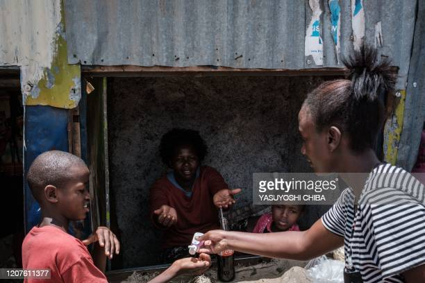 Volunteer of local NGO Shining Hope for Communities provide hand disinfectant to a boy as a preventive measure for the COVID-19 coronavirus at the...