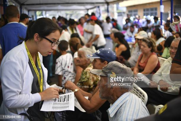 A volunteer of the Aid and Freedom Coalition movement assists people seek medical attention in the Macarao neighbourhood in Caracas on February 17...