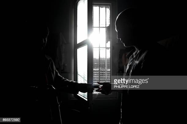 A volunteer of the Christian charity organization 'Secours Catholique' holds a pack of cigarettes as distributing Christmas gifts to inmates on...