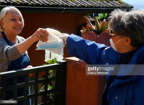 A volunteer of the Italian Red Cross distributes free protective masks to Florence resident to contain the spread of the COVID19 pandemic caused by...