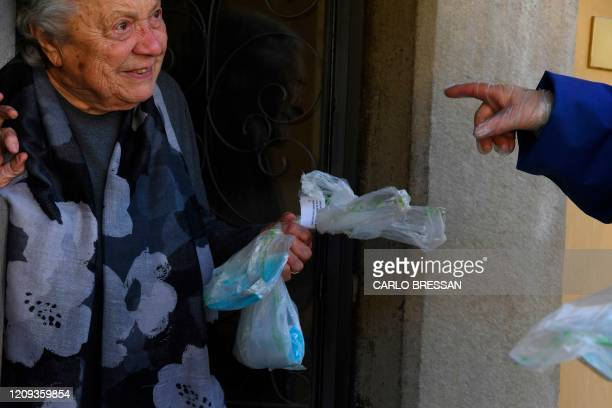 Volunteer of the Italian Red Cross distributes free protective masks to Florence resident to contain the spread of the COVID-19 pandemic, caused by...