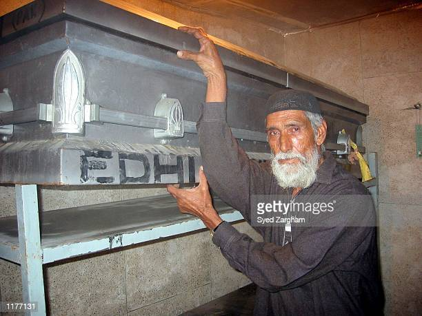 Volunteer of the private humanitarian organization, Edhi Welfare Trust, shows the coffin containing the alleged remains of U.S. Journalist Daniel...