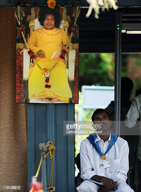 A volunteer of The Satya Sai Baba Ashram looks on as he sits near an image of Sathy Sai Baba at the entrance to his Ashram after his death was...