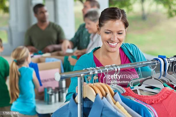 Volunteer organizing racks of clothing at charity donation drive