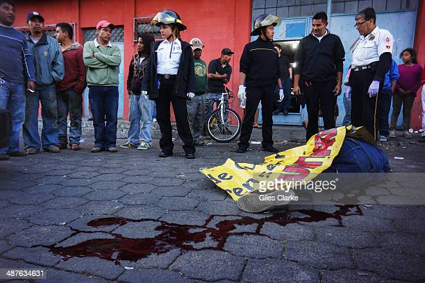 A volunteer paramedic checks the vitals of a man who was shot in the head while entering his house January 16 2014 in Guatemala City Guatemala The...