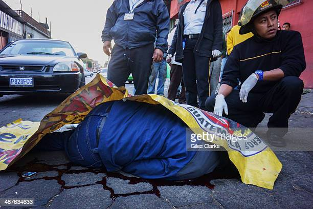 CITY GUATEMALA A volunteer paramedic checks the vitals of a man who was shot in the head while entering his house JANUARY 16 January 16 2014 in...
