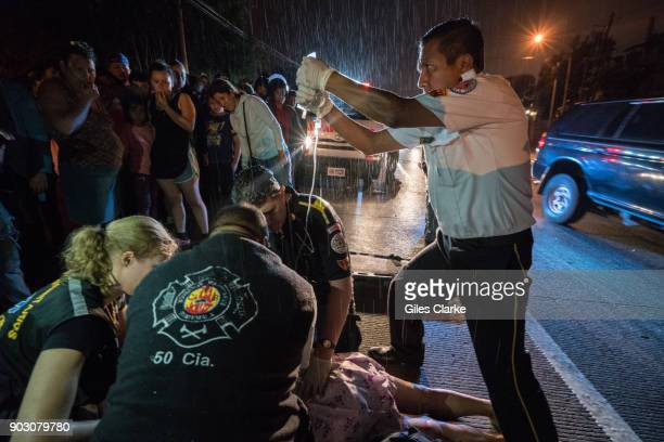 A volunteer paramedic holds an IV over Dr Chiu for a badly injured woman who was a victim of a hit and run driver She died shortly after on the scene...