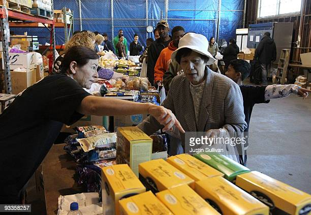 A volunteer passes out boxes of stuffing for a Thanksgiving meal November 24 2009 at the Alameda Food Bank in Alameda California Hundreds of needy...